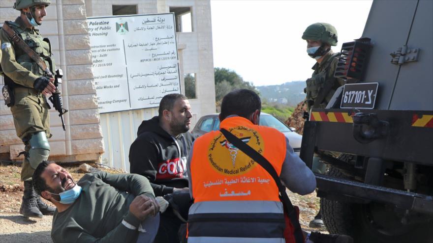 Soldados israelíes llegan para arrestar a un manifestante palestino herido en Cisjordania, 4 de diciembre de 2020. (Foto: AFP)