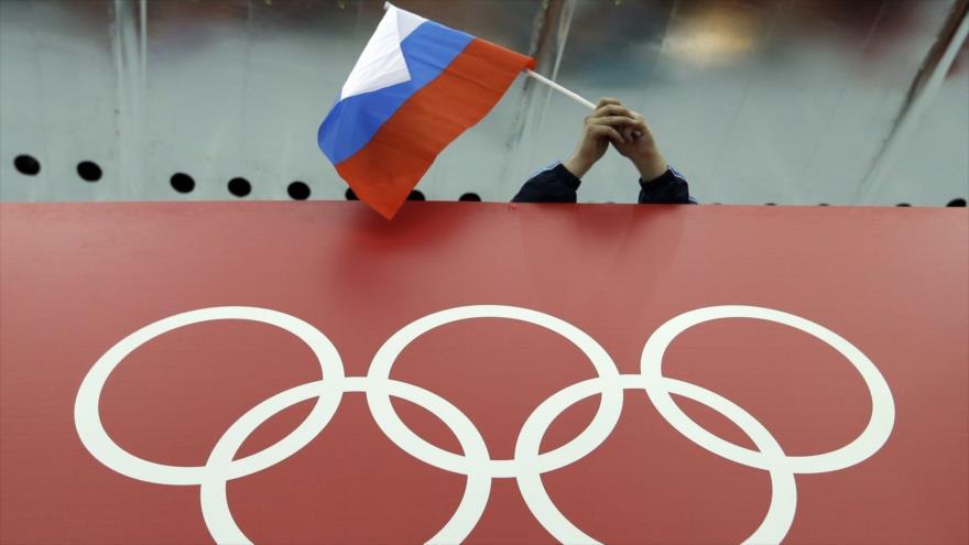 Una bandera rusa se sostiene sobre los anillos olímpicos durante los Juegos Olímpicos de Invierno en Sochi (Rusia), 18 de febrero de 2014. (Foto: AP).