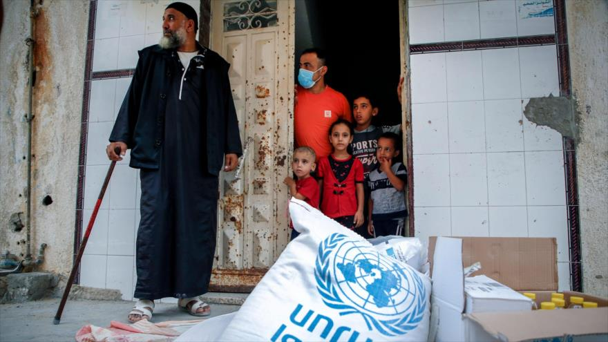 Miembros de una familia palestina esperan recibir ayuda alimentaria proporcionada por la UNRWA en Gaza, 15 de septiembre de 2020. (Foto: AFP)