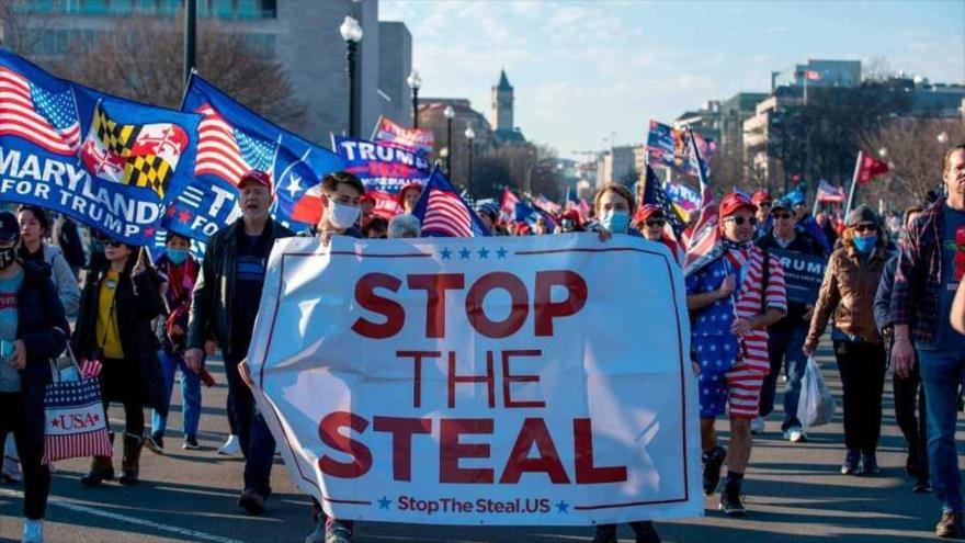 """Partidarios del actual presidente en funciones de EE.UU., Donald Trump, sujetan una pancarta en la que se lee """"Detengamos el Robo"""" en una marcha a su favor."""