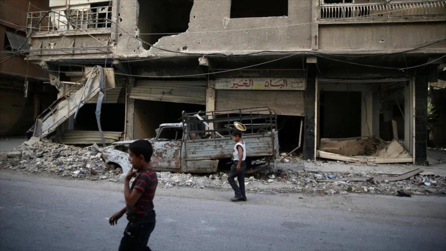 Niños caminan cerca de edificios dañados en Ain Tarma, suburbio de Damasco, capital siria. (Foto: Reuters)