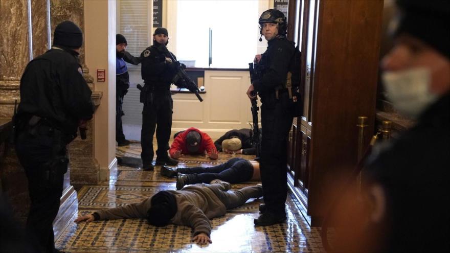 Oficiales de policía detienen a simpatizantes de Donald Trump tras un asalto al Capitolio, 6 de enero de 2021. (Foto: AFP)