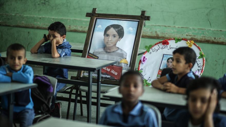 Los niños de Gaza se sientan en un aula cerca de una foto de su compañero de clase Moath al-Sawarka, de 7 años, uno de los cinco niños muertos en un ataque aéreo israelí dos días antes, 16 de noviembre de 2019.