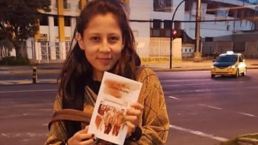 """Una adolescente latinoamericana posa para una foto con el libro """"Mi tío Soleimani""""."""