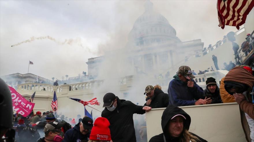 Partidarios de Trump se protegen el rostro para evitar inhalar los gases lacrimógenos lanzados por policías al frente del Capitolio de EE.UU., 6 de enero de 2021. (Foto: Reuters)