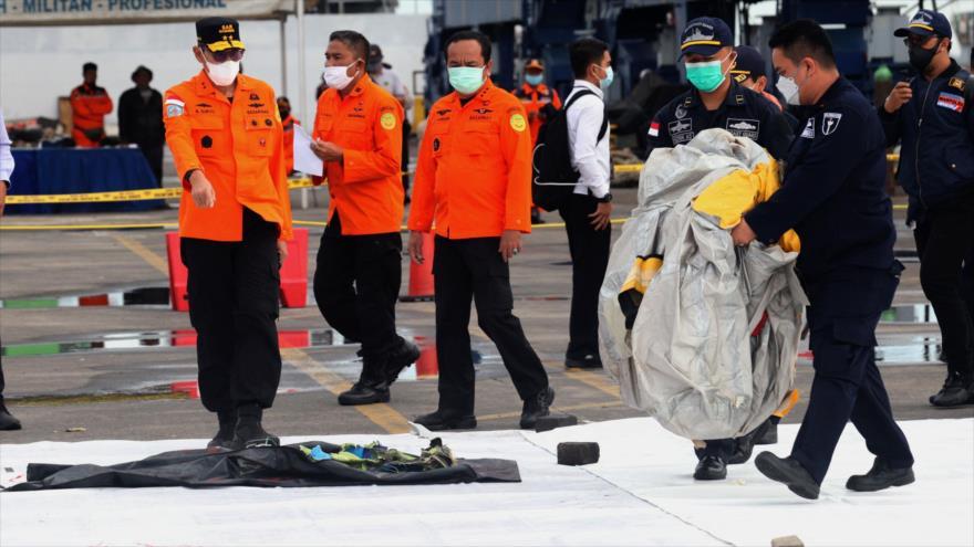 Equipos de rescate trasladan escombros de un avión siniestrado en el puerto de Yakarta, en Indonesia, 10 de enero de 2021. (Foto: AFP)
