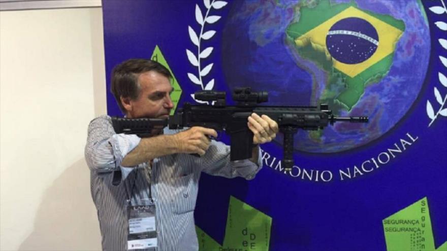 Presidente de Brasil, Jair Bolsonaro, en posición de tiro en la prueba de un rifle.