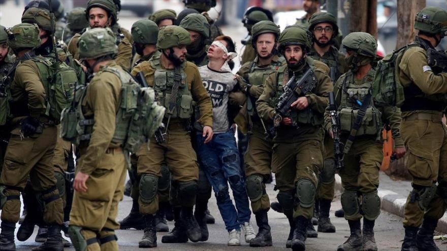 Soldados israelíes detienen a un niño palestino en Hebrón por participar en una protesta contra el régimen de ocupación, diciembre de 2017.