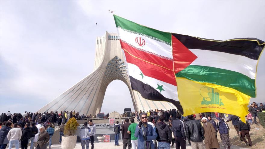 Un iraní sostiene las banderas de Irán, Palestina, Siria y el movimiento libanés Hezbolá durante la marcha por el aniversario de la Revolución Islámica de Irán.