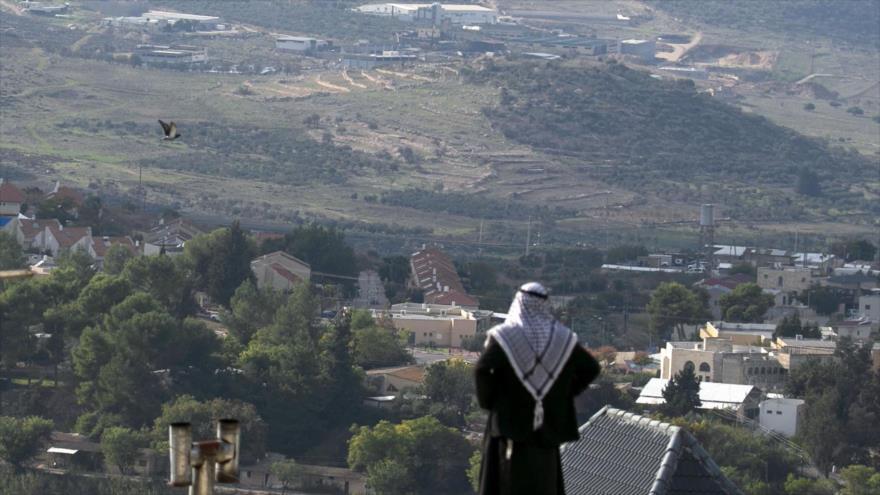Un palestino mira hacia la colonia israelí construida junto al pueblo palestino de Naqoura en la ocupada Cisjordania, 23 de noviembre de 2020. (Foto: AFP)