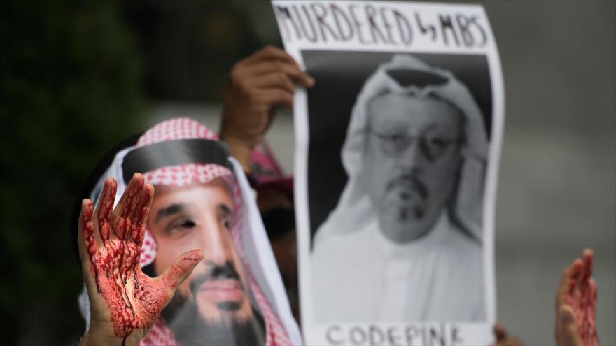 Un hombre sostiene una imagen del periodista Jamal Khashoggi, sugiriendo que su asesinato fue por orden del príncipe heredero saudí, Muhamad bin Salman Al Saud.