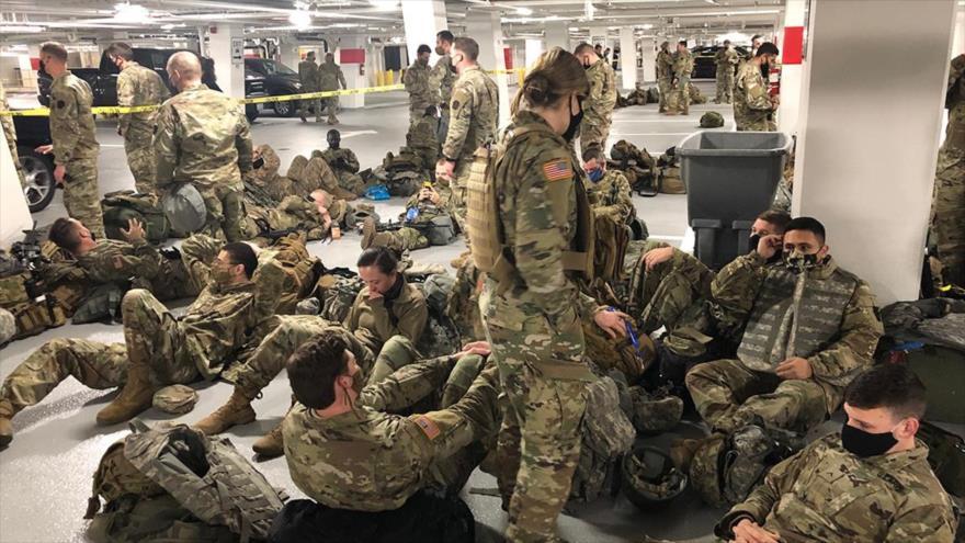 Algunos miembros de la Guardia Nacional duermen en el suelo de un aparcamiento cerca del Capitolio de EE.UU., 21 de enero de 2021. (Foto: POLITICO)