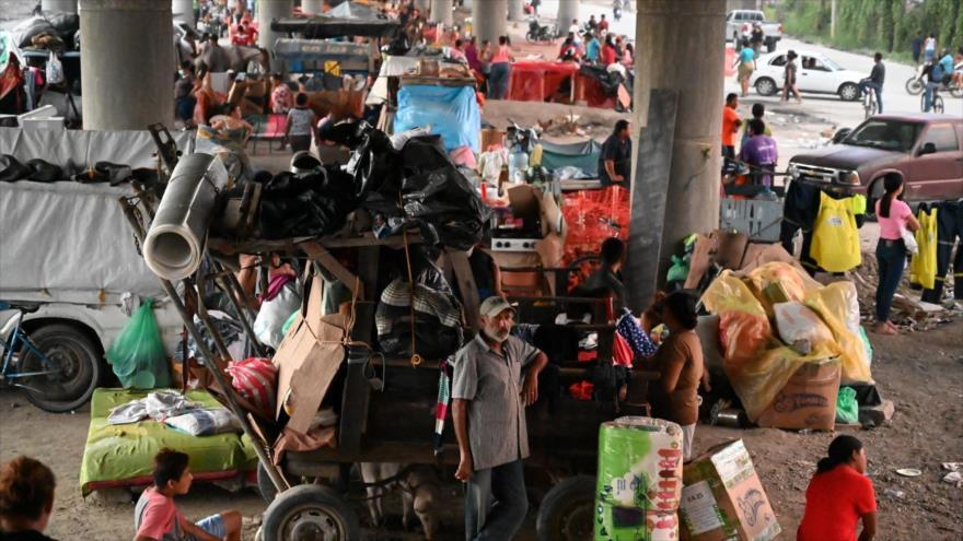 La gente permanece debajo de un puente tras el paso del huracán Iota en San Pedro Sula, 21 de noviembre de 2020. (Foto: AFP)