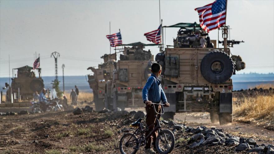 Un niño sirio en su bicicleta mira a un convoy de vehículos blindados de EE.UU. cerca de la ciudad Al-Qahtaniyah (norte), 31 de octubre de 2019. (Foto: AFP)