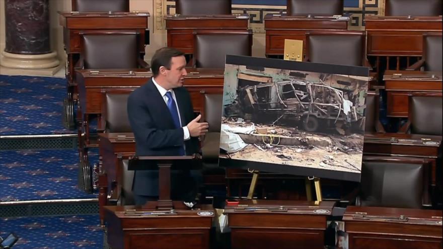Chris Murphy muestra la imagen de un autobús escolar yemení destruido en un ataque saudí durante una sesión del Senado de EE.UU., 28 de enero de 2021.