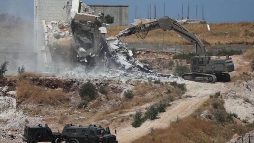 Maquinaria israelí demuele un edificio palestino en la aldea del Sur Baher en Cisjordania, 22 de julio de 2019. (Foto: Reuters)