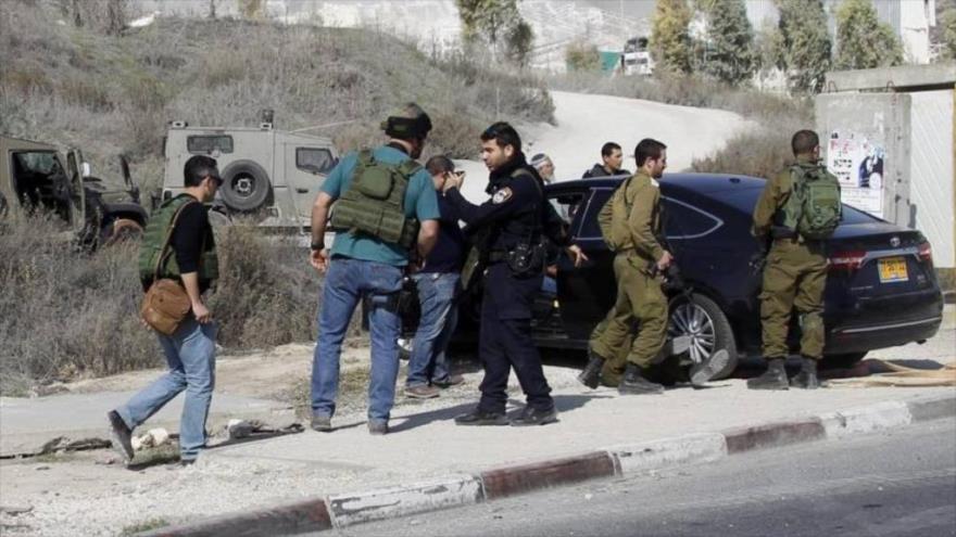 Soldados y policías de Israel inspeccionan el automóvil de un colono israelí que atropelló a una palestina en la ocupada Cisjordania.