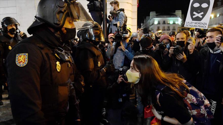 Un grupo de manifestantes congregados en la Puerta del Sol de Madrid porta pancartas en apoyo al rapero catalán encarcelado Pablo Hasél, 17 de febrero de 2021. (Foto: AFP)