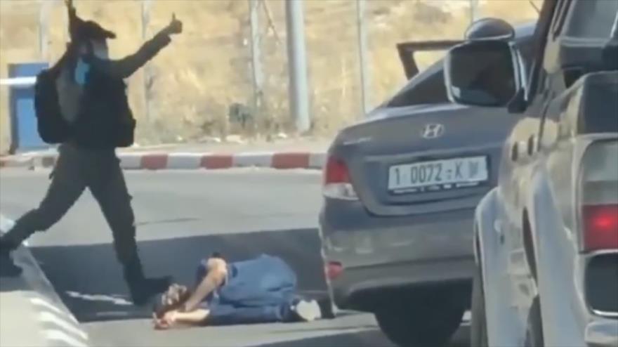 Un militar israelí levanta el pulgar junto al joven palestino asesinado, Ahmed Erekat.
