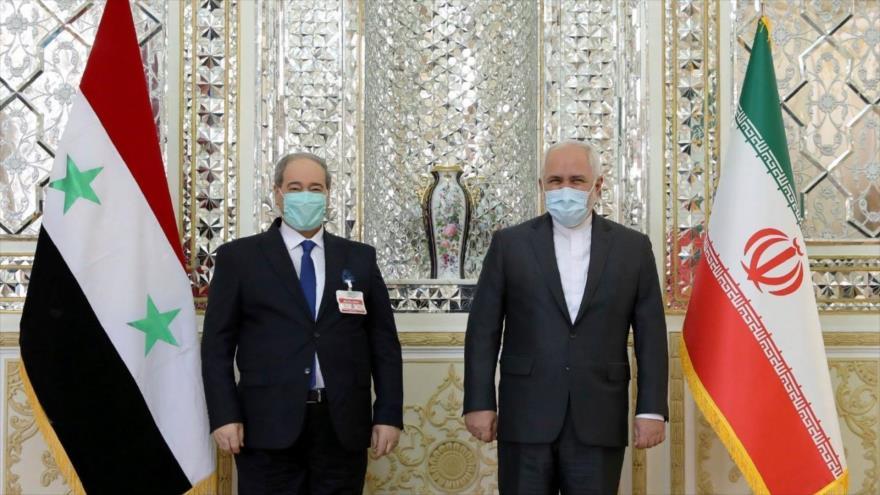El canciller iraní, Mohamad Yavad Zarif (dcha.), reunido con su homólogo sirio, Faisal al-Miqdad, en Teherán, capital persa, 7 de diciembre de 2020.