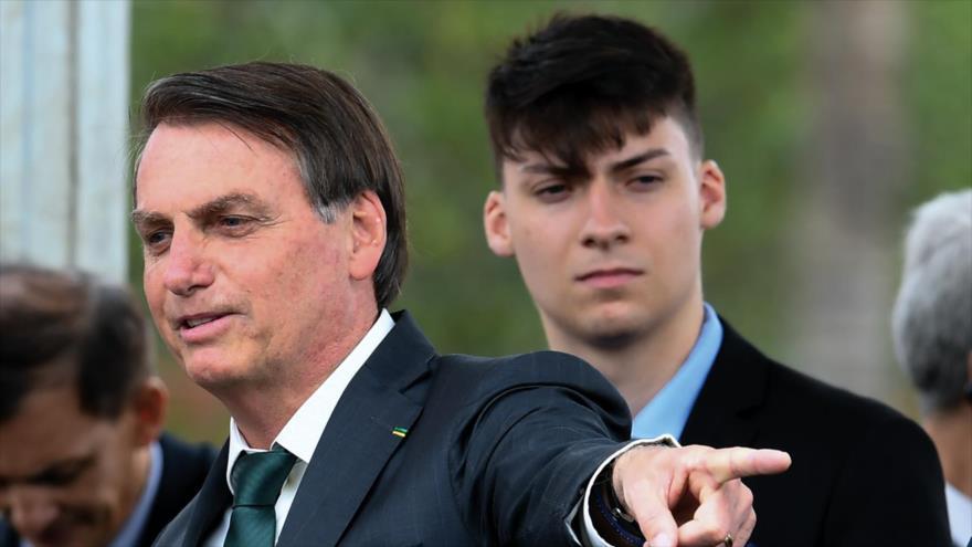 El presidente brasileño, Jair Bolsonaro (izda.), y su hijo menor, Renan Bolsonaro. (Foto: AFP)