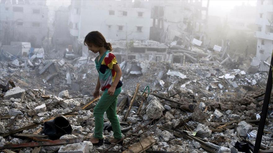 Una niña palestina camina sobre los escombros de su casa destruida por el régimen de Israel en Gaza, 27 de agosto de 2014. (Foto: AFP)