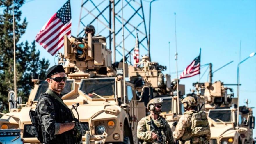 Un miembro de las Unidades de Protección Popular, junto a soldados de EE.UU. cerca de un pozo petrolero en Al-Hasaka, noreste de Siria.