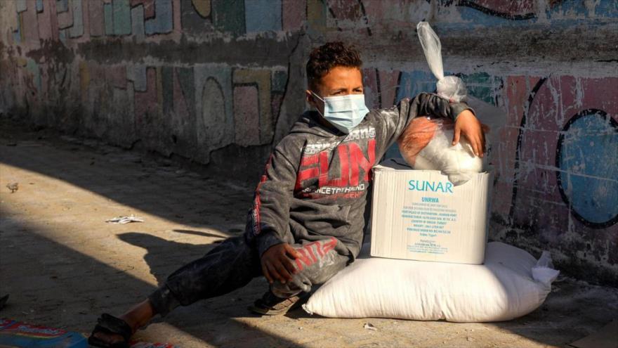 Un niño palestino sentado junto a paquetes de ayuda humanitaria en la Franja de Gaza, 31 de enero de 2021. (Foto: AFP)