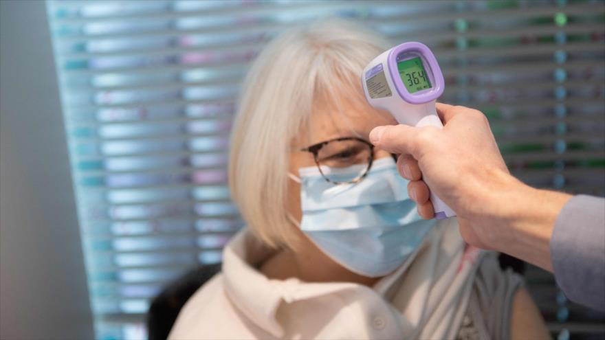 Un farmacéutico toma la temperatura de un paciente en un centro médico en París, Francia, 12 de marzo de 2021. (Foto: AFP)