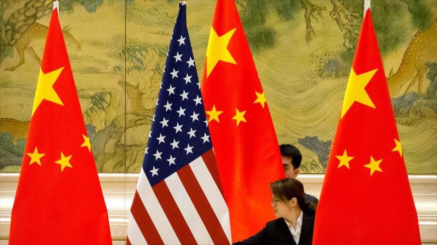 Una bandera de EEUU y tres de China antes de un encuentro entre funcionarios de ambos países en Pekín, 14 febrero de 2019.