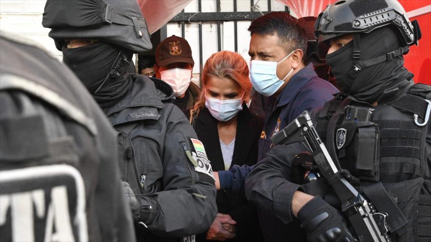 La expresidenta de facto de Bolivia, Jeannine Áñez, es escoltada por los policías luego de ser arrestada en La Paz, 13 de marzo de 2021. (Foto: AFP)