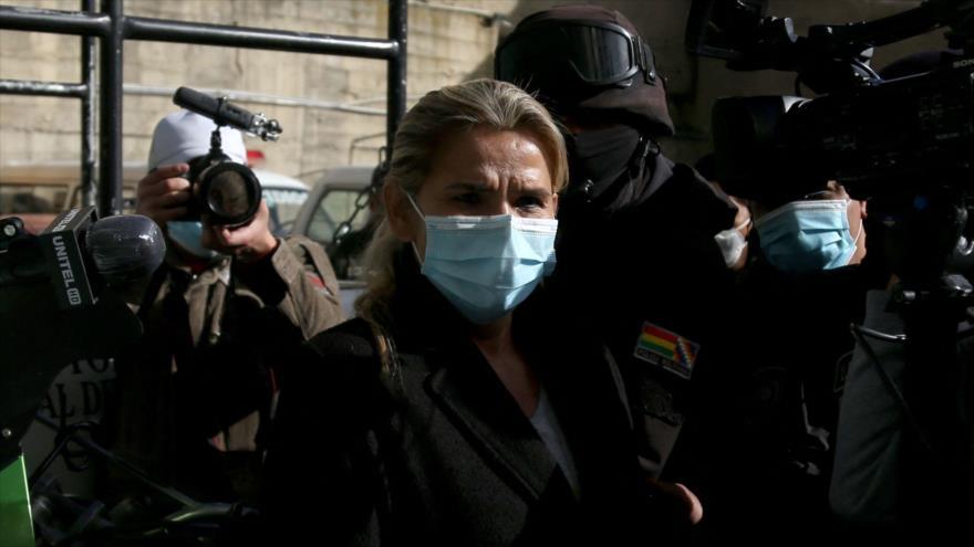 La expresidenta de facto de Bolivia, Jeannine Áñez, es escoltada por los policías luego de ser arrestada, La Paz, 13 de marzo de 2021. (Foto: AFP)