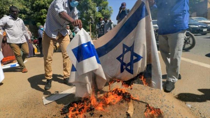 Sudaneses queman la bandera israelí en una protesta en Jartum, la capital, 17 de enero de 2021. (Foto: AFP)