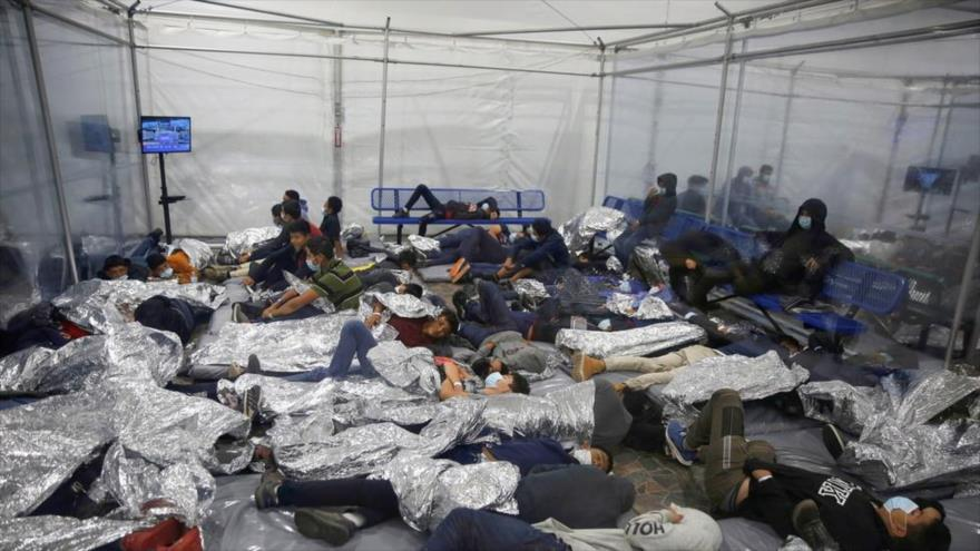 Un grupo de menores migrantes dirimiendo sobre suelo en una cabina montada bajo una carpa de las dependencias del centro de detención de la Oficina de Aduanas y Protección Fronteriza de EE.UU. (CBP) en Donna, situado en el estado de Texas. (Foto: CBS)