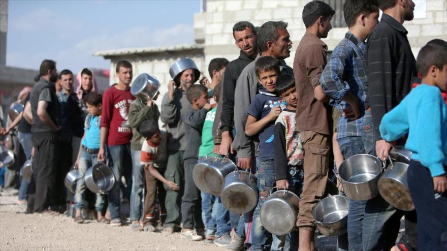 Desplazados sirios del este de Guta hacen cola para obtener comida en el refugio de Herjelleh en el campo de Damasco.