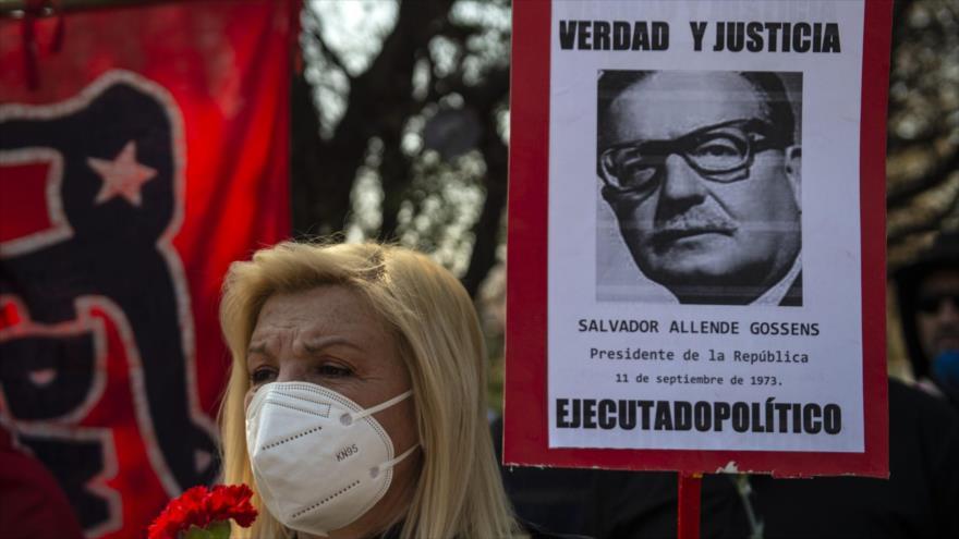 Una mujer sostiene un cartel con la imagen del expresidente chileno Salvador Allende en Santiago, capital, 11 de septiembre de 2020. (Foto: AFP)