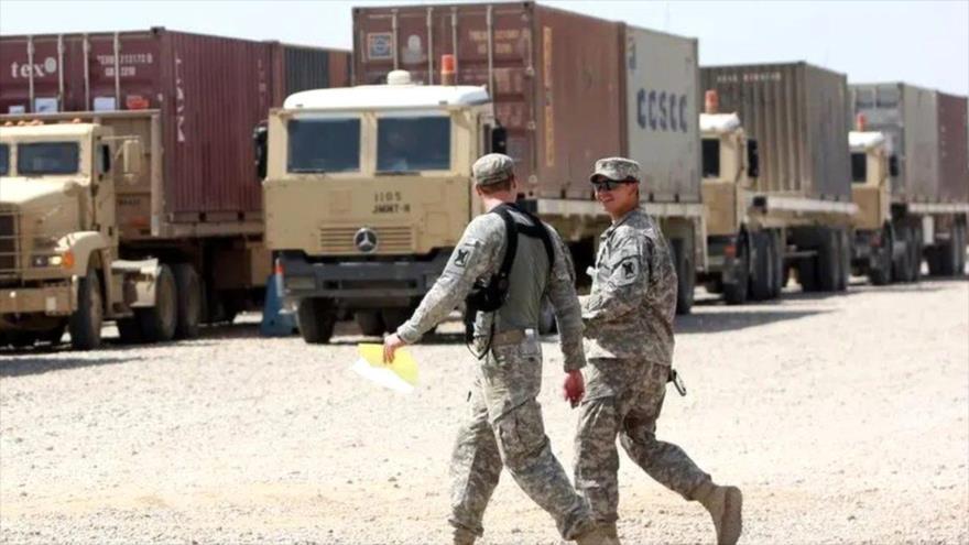 Soldados estadounidenses pasan junto a camiones en la base aérea Al-Balad, Irak. (Foto: AFP)