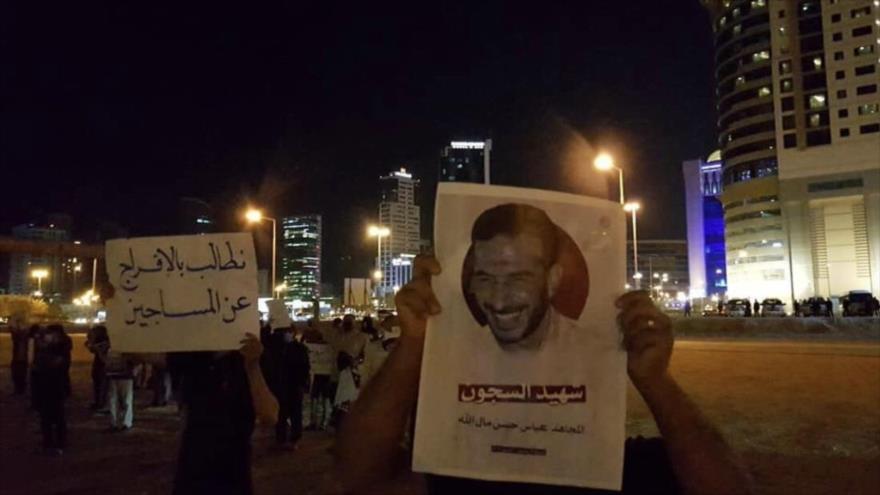 Manifestantes sostienen pancartas y fotos de Abbas Al Allah, un preso bareiní que murió por negligencia médica, 6 de abril de 2021. (Foto: Al-Wefaq)