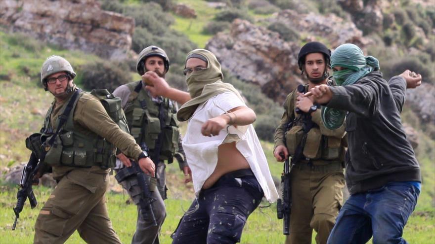Colonos israelíes lanzan piedras contra los palestinos.