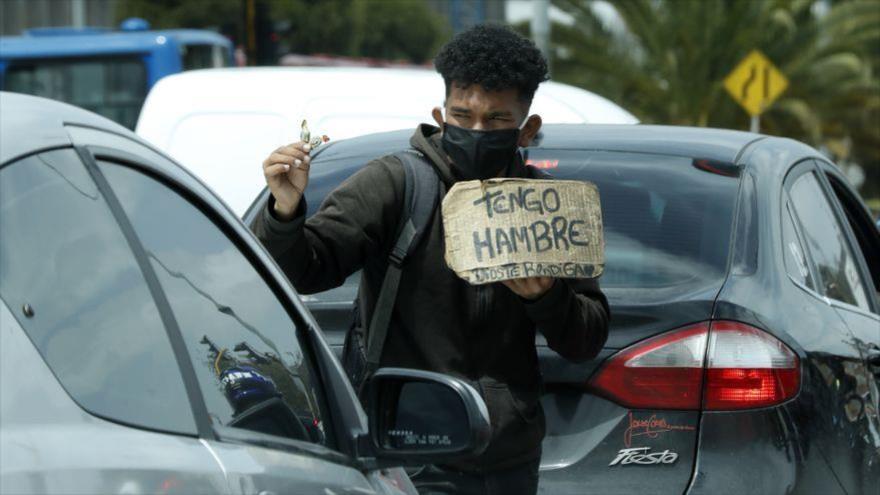 Un muchacho colombiano mendigando entre los coches en el tráfico de Bogotá, capital de Colombia.