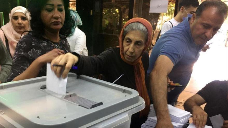 Una mujer siria está ingresando su voto en la urna. Elecciones parlamentarias, Damasco, Siria. 19 de julio de 2020, (Foto: Reuters)