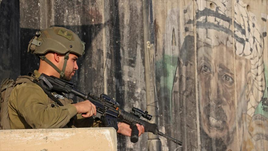 Un soldado israelí hace guardia mientras los palestinos esperan en el puesto de control cerca de la ocupada Cisjordania, 30 de abril de 2021. (Foto: AFP)
