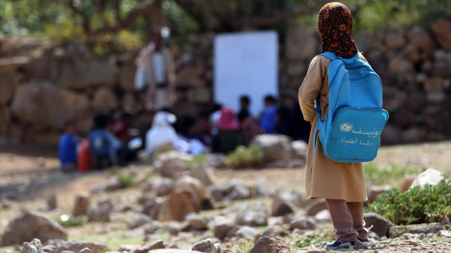 Una niña yemení con mochila entregada por Unicef observa una clase al aire libre en una zona en la provincia de Taez, 16 de septiembre de 2019.