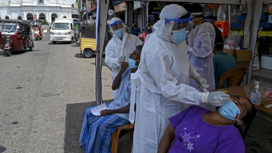 Trabajadores de salud recolectan muestras de hisopos de los residentes para realizar pruebas del coronavirus en Sri Lanka, 4 de mayo de 2021. (Foto: AFP)