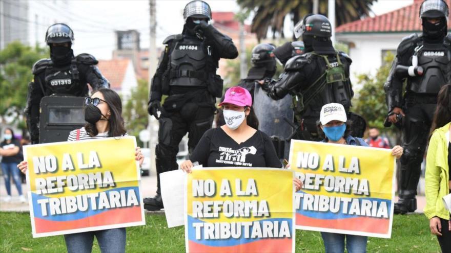 """Mujeres colombianas sostienen pancartas que dicen """"No a la reforma tributaria"""" durante una protesta antigubernamental."""