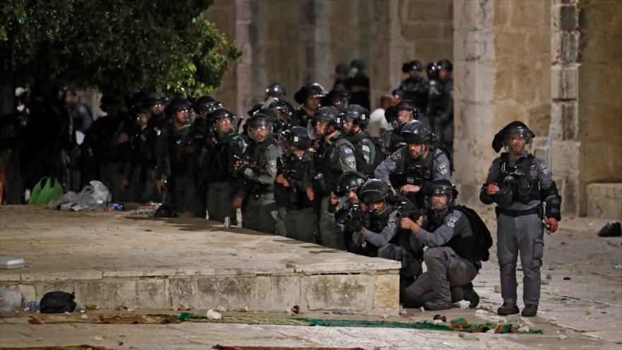 Un grupo de fuerzas de seguridad israelí se agolpa cerca de uno de los accesos a la Mezquita de Al-Aqsa en Al-Quds (Jerusalén), 7 de mayo de 2021. (Foto: AFP)