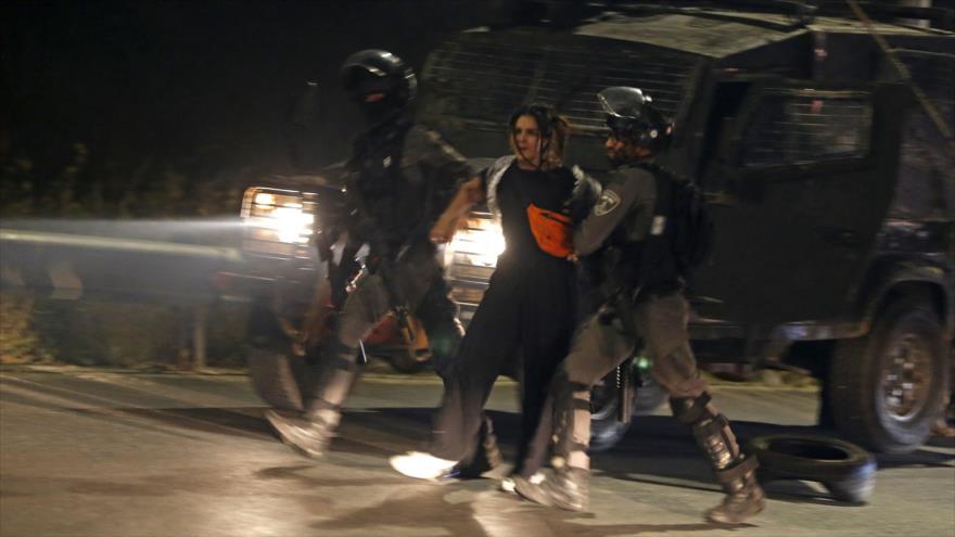 Dos soldados israelíes arrestan a una mujer palestina durante una protesta en Cisjordania. 10 de mayo de 2021. (Foto: AFP)