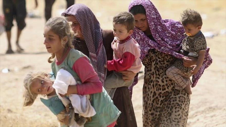 Mujeres izadíes con sus hijos en brazo tratan de huir las violencias del grupo terrorista Daesh en Irak.