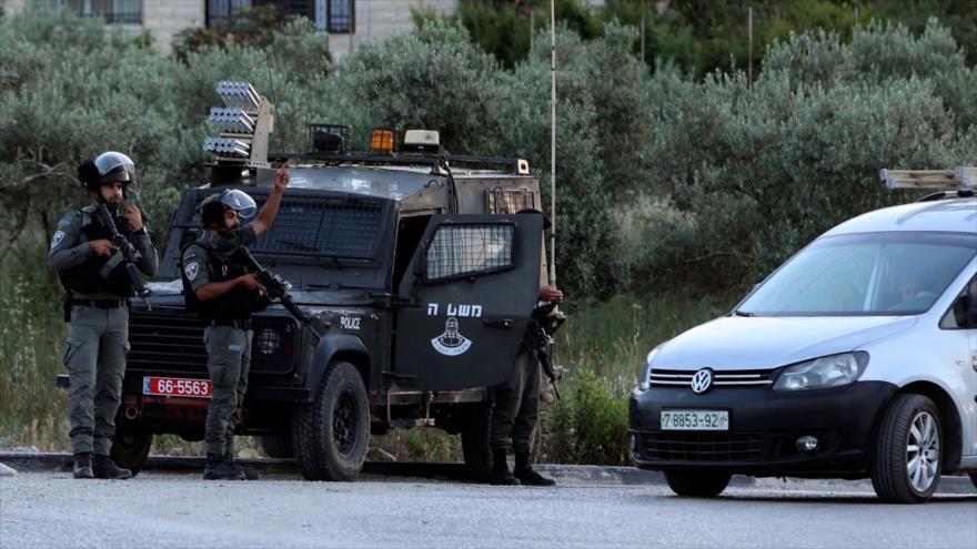 Policía israelí detiene un vehículo civil palestino en el cruce de Zaatara al sur de la ciudad de Nablus en la ocupada Cisjordania, 11 de mayo de 2021. (Foto: AFP)