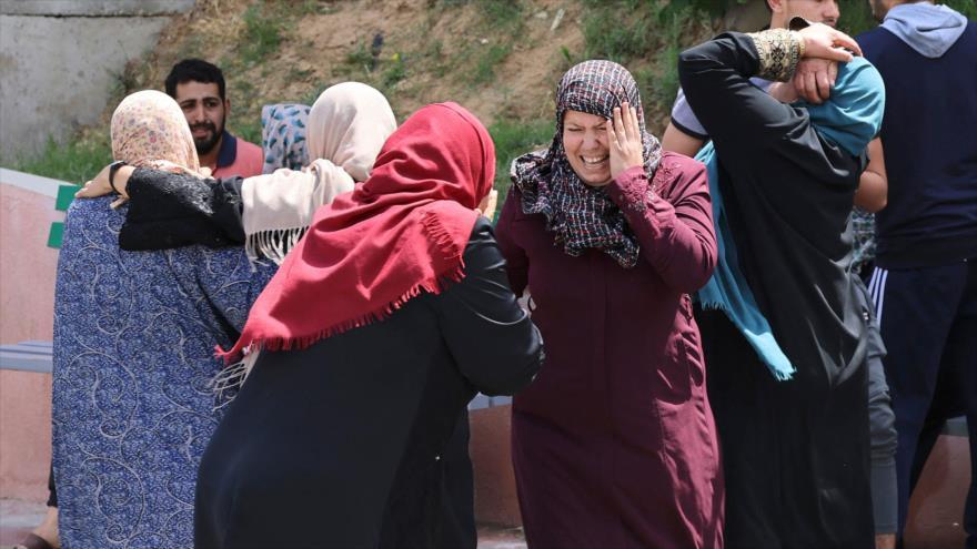 Palestinos reaccionan ante la muerte de familiares en Beit Lahia, tras ataques aéreos israelíes en Gaza, 12 de mayo de 2021. (Foto: AFP)